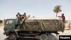 متطوعون في بغداد تنقلهم عربة عسكرية لمحاربة داعش 12/06/2014