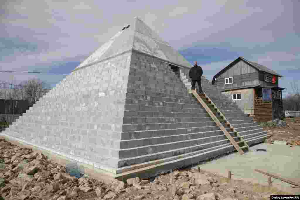 Andrei Vakhrushev stands at the entrance to his pyramid, which he built on the grounds of his rural house in the Russian village of Istinka, outside St. Petersburg. (AP/Dmitri Lovetsky)