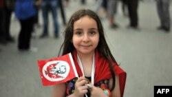 Мустафа Кемал Ататүрктүн сүрөтү түшүрүлгөн желекче көтөргөн кыз. Стамбул, 2013-жыл.