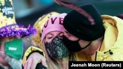 Egy férfi csókolja meg párját Szilveszter éjjelén maszkban New Yorkban. 2020. december 31.