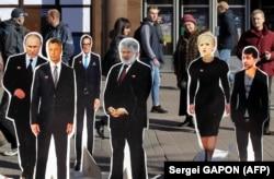 Люди дивляться на картонні зображення реальних і прихованих імовірних головних «гравців» виборчої кампанії 2019 року