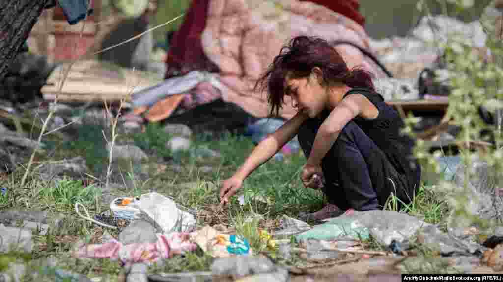Дівчинка зі стихійного поселення ромів палить багаття з целофанових пакетів