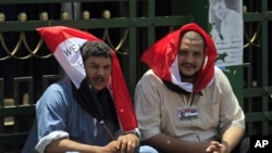 Egyptian protesters cover their heads from the sun with Egyptian flags, as they protest in Tahrir Square in Cairo on July 12, 2011