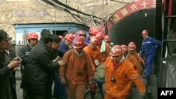 A TV screen grab shows rescuers carrying a miner away from the mine on a stretcher.