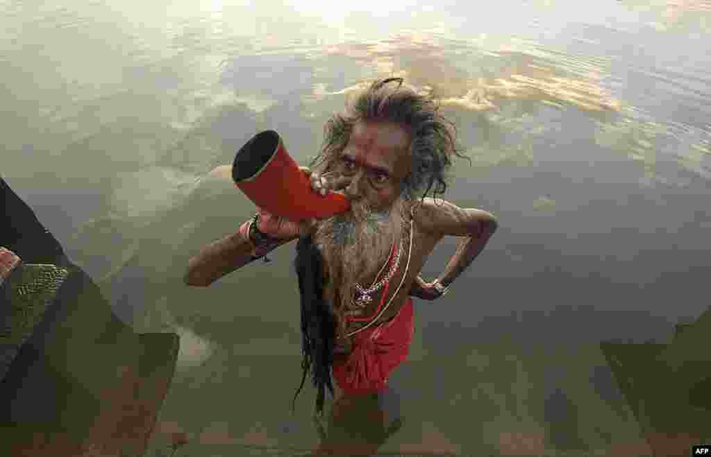 "An Indian ""sadhu,"" or holy man, blows a buffalo horn on the eve of the traditional Kharchi Puja festival at Agartala, the capital of the northeastern Indian state of Tripura. (AFP/Arindam Dey)"