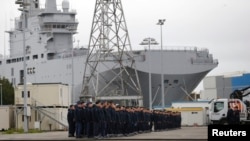"Russian sailors gather in front of the Mistral-class helicopter carrier ""Vladivostok"" at the STX Les Chantiers de l'Atlantique shipyard site in Saint-Nazaire on December 17."