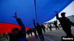 People march on the street with a giant Russian flag in Simferopol, Crimea.