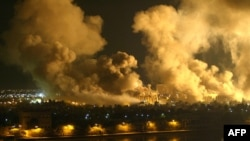 Smoke covers the presidential palace compound during a massive U.S.-led air raid on Baghdad on March 21, 2003.