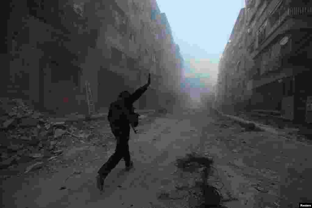 A rebel fighter gestures as he runs across a street during what the rebel fighters said was an offensive against them by Syrian government forces in the Mleha suburb of Damascus. (Reuters/Bassam Khabieh )