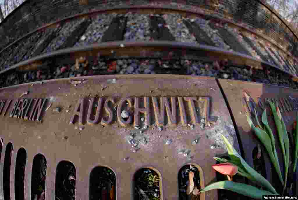 A flower is seen next to the word 'Auschwitz' at the Gleis 17 (Platform 17) memorial, a platform at Berlin-Grunewald train station from where Jewish citizens were deported by train to the Nazi concentration camps between 1941 and 1945, in Berlin, Germany, January 27, 2021. REUTERS/Fabrizio Bensch