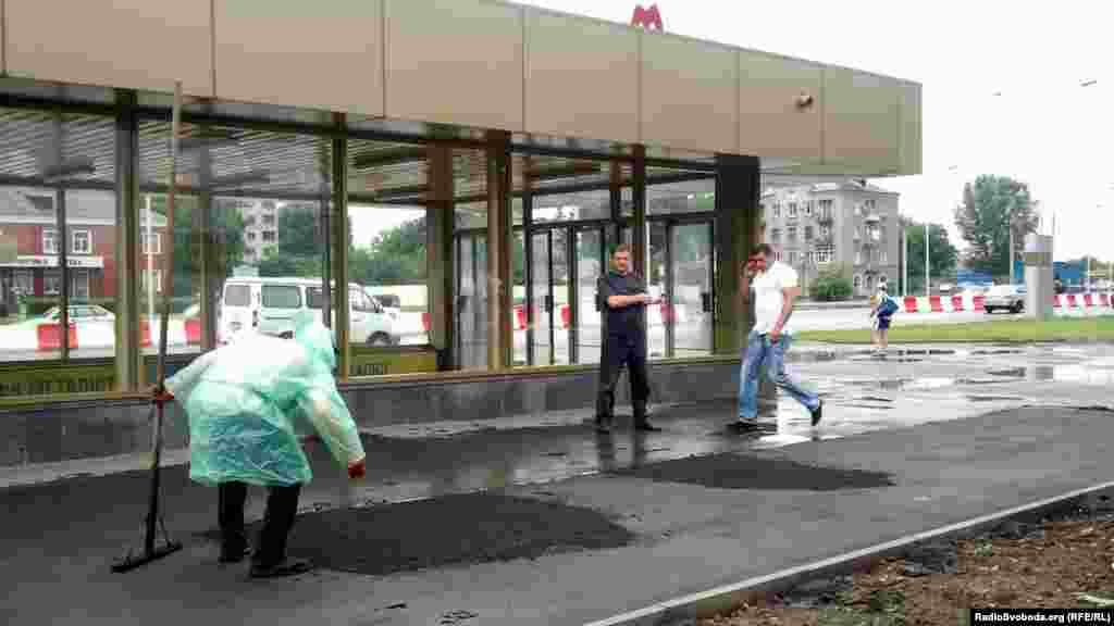 Біля станції метро «Спортивна» робітники кладуть новий асфальт