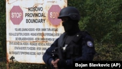 With rising tensions, a Kosovo police officer stands guard at the border crossing of Jarinje on September 20.