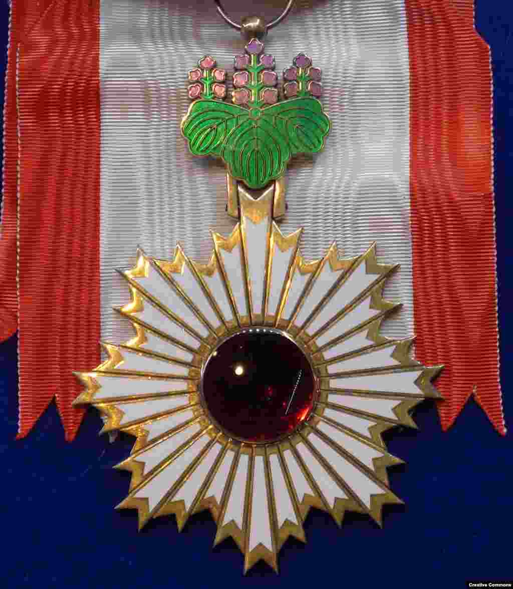 Japan's Order of the Rising Sun   The handmade medal represents a dawn sun made from a polished garnet stone surrounded by a star made of gold and enamel which is suspended from the leaf of a Paulownia tree.