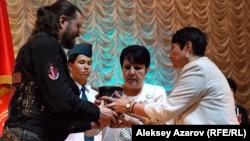 Член байкерского клуба «Ночные волки» Алексей Вайц вручает внучкам генерал-майора Ивана Панфилова Айгуль и Алуа Байкадамовым капсулу с землей. Алматы, 10 мая 2015 года.