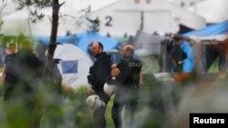 Греческие полицейские рядом с лагерем беженцев в поселке Идомени. 24 мая 2016 года.