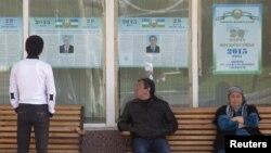Президент сайлауына кандидаттар туралы ақпарат ілінген жердегі адамдар. Ташкент, 26 наурыз 2015 жыл. (Көрнекі сурет)
