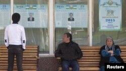 Люди смотрят на предвыборные плакаты кандидатов в президенты. Ташкент, 26 марта 2015 года.