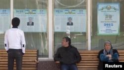 Люди смотрят на предвыборные плакаты кандидатов в президенты Узбекистана. Ташкент, 26 марта 2015 года. Иллюстративное фото.