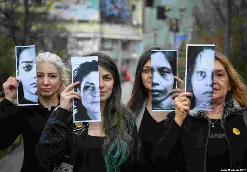 Activists of the Declic movement for women's rights hold printed half-face pictures showing victims of domestic violence during a protest in Bucharest on March 4. (AFP/Daniel Mihailescu)