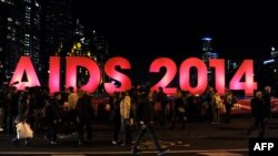Australia -- People gather next to a sign reading AIDS 2014 in Melbourne, July 18, 2014