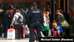 Сотрудник полиции наблюдает, как прибывшие на вокзал мигранты выходят из поезда. Мюнхен, 5 сентября 2015 года.