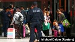 Немецкий полицейский наблюдает за прибытием поезда с беженцами. Мюнхен, 5 сентября 2015 года