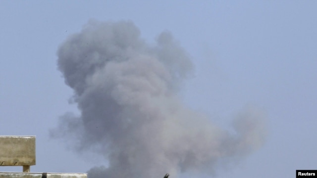 Smoke rises after a NATO and coalition air strike in Tripoli on April 14.