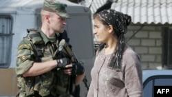Чеченка проходит мимо российского военного. Грозный, 24 сентября, 2004