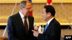 Russian Foreign Minister Sergei Lavrov (left) talks with his Japanese counterpart Fumio Kishida at the start of their meeting on March 20.