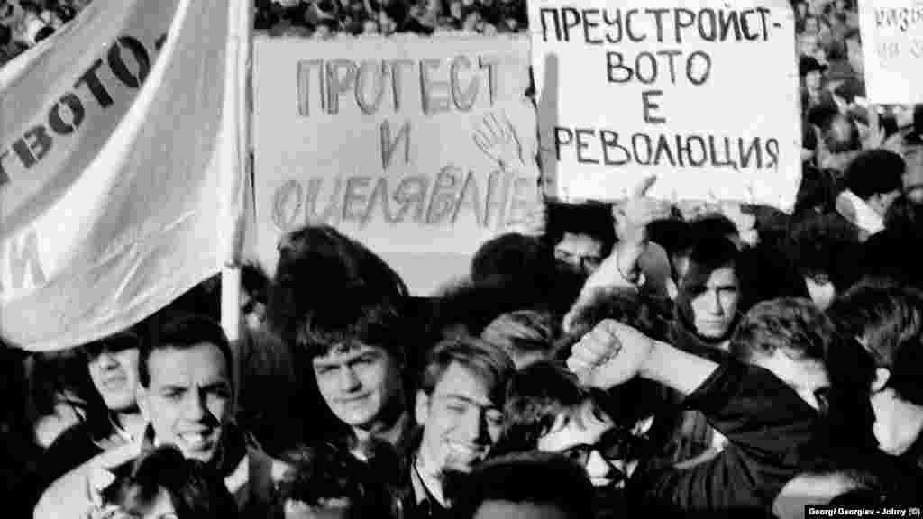 """Емоциите се отпушват чак на осмия ден, 18.11.1989 г. Тогава опозицията провежда първия си митинг - пред Св. """"Александър Невски"""". Тогава тя не се нарича """"опозиция"""", изразът е """"неформални сдружения"""". Хората отиват на митинга с разнородни и понякога несъвместими лозунги и искания. Част от плакатите отразяват тогавашната нагласа на много участници, че в България ще започне да се извършва преустройство, каквото протича в СССР от няколко години."""