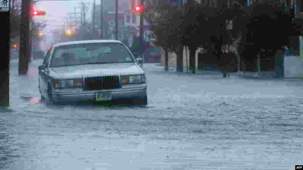 A car sits in a flooded street near the ocean ahead of Hurricane Sandy in Atlantic City, New Jersey.