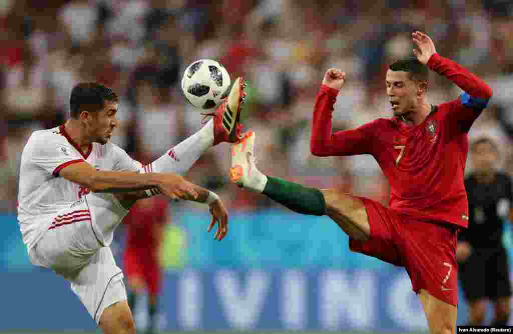 Iran's Majid Hosseini (left) competes for the ball with Portugal's Cristiano Ronaldo in their countries' World Cup group game in Saransk, Russia, on June 25. (Reuters/Ivan Alvarado)