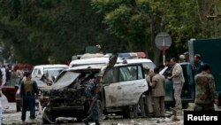 Afghan police investigate the site of a bomb attack against presidential candidate Abdullah Abdullah's motorcade.