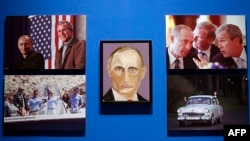 """U.S. -- A portrait of Vladimir Putin, President of Russia painted by former president George W. Bush is displayed between photographs as part of the exhibit, """"The Art of Leadership: A President's Personal Diplomacy"""" at the George W. Bush Presidential Libr"""