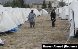 FILE: Men with face masks spray near tents used as a quarantine facility in Balochistan.