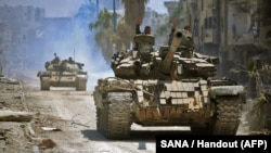 A handout picture released by the official Syrian Arab News Agency on May 14 shows government forces head towards militant positions in the Hajar al-Aswad district on the southern outskirts of Damascus.