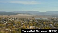 Поселок раскинулся у одноименной горы, вдалеке блестят огромные теплицы