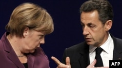 French President Nicolas Sarkozy (right) and German Chancellor Angela Merkel following crisis talks with Greek Prime Minister George Papandreou in Cannes.