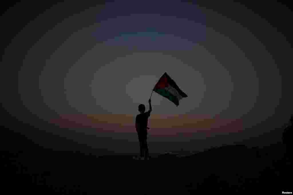 A boy waves a Palestinian flag at the Israel-Gaza border amid heightened tensions after deadly clashes involving Israeli troops and protesters. (Reuters/Mohammed Salem)