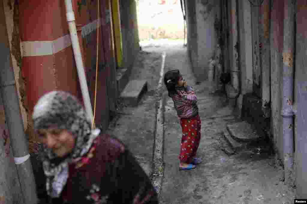 A girl laughs in a street next to frontline positions of Iraqi Federal Police fighting the Islamic State in Mosul on April 2. (Reuters/Andres Martinez Casares)