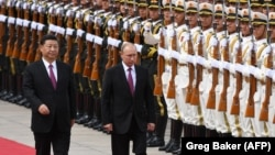 Russian President Vladimir Putin (right) reviews a military honor guard with Chinese President Xi Jinping during a welcoming ceremony outside the Great Hall of the People in Beijing on June 8.