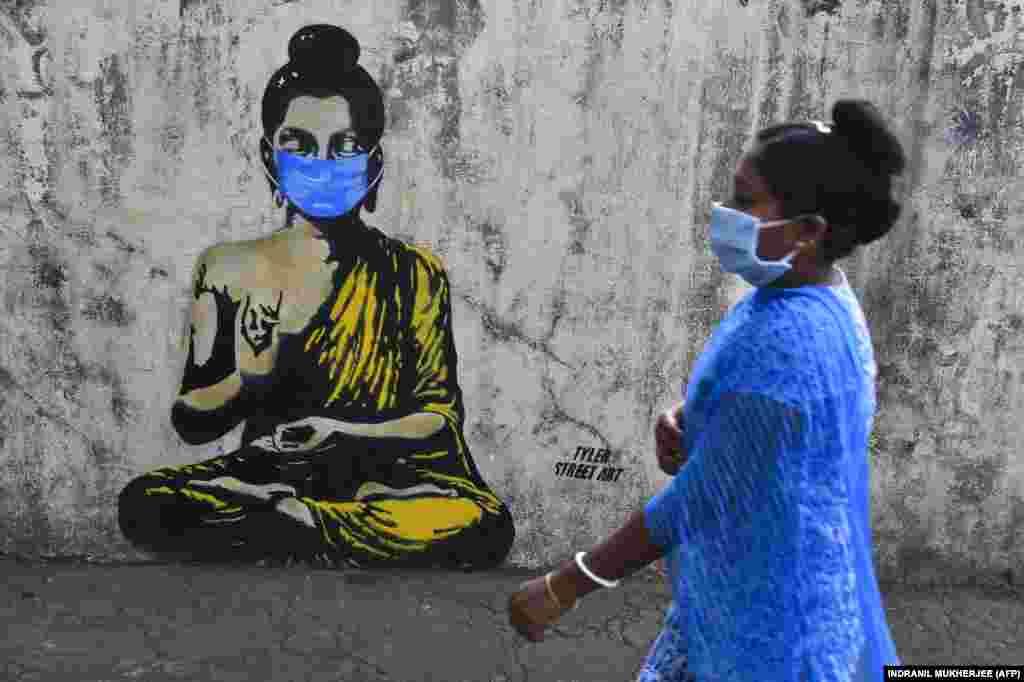 Жителка на Мумбай, Индия, минава пред изображение на Буда, носещ маска.