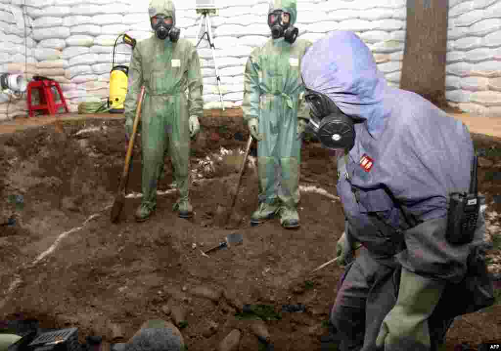 A Chinese chemical-weapons disposal team excavates chemical bombs from a site near a school in the northeastern Chinese city of Mudanjiang in 2006. Japananese soldiers left hundreds of thousands of mustard-gas bombs and other such weapons in China at the end of World War II. It is considered the world's largest stockpile of abandoned chemical weapons.