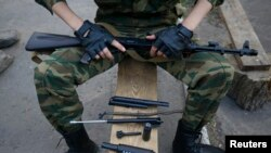 A pro-Russian fighter lays out parts from some of his weapons in eastern Ukraine on May 23.