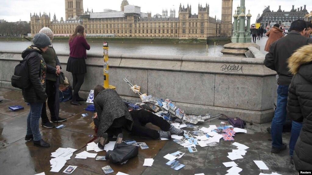 Жүргіншілер шабуылдан жараланған адамға көмектесіп жатыр. Лондон, 22 наурыз 2017 жыл.