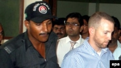 Pakistani police escort Joel Cox (right) to court in Karachi on May 6.