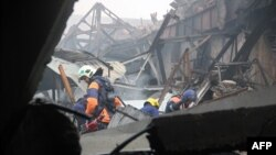 Eemergency services work amid the debris of a shopping mall, which was razed by fire in Kazan.