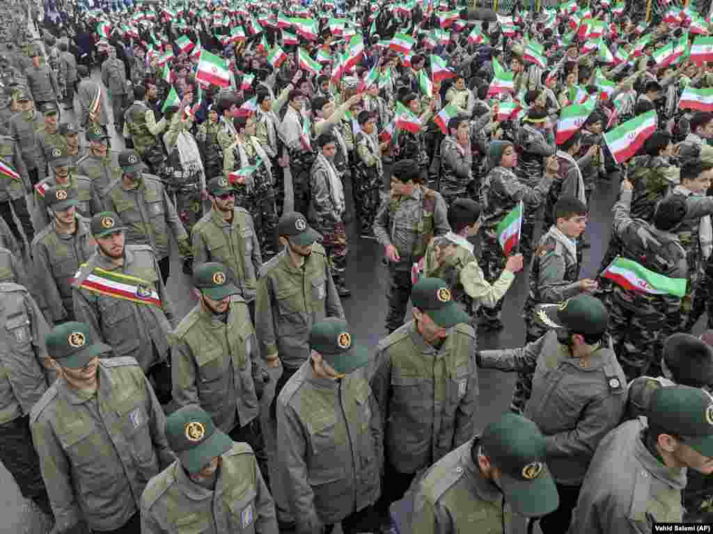 School students wave national flags as Islamic Revolutionary Guards Corps members arrive in Azadi (Freedom) Square.