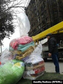 Yanğından salamat qalan əşyalarını – yorğan –döşəyi, pal-paltarı sellofan torbalara doldurub daşıyırlar.