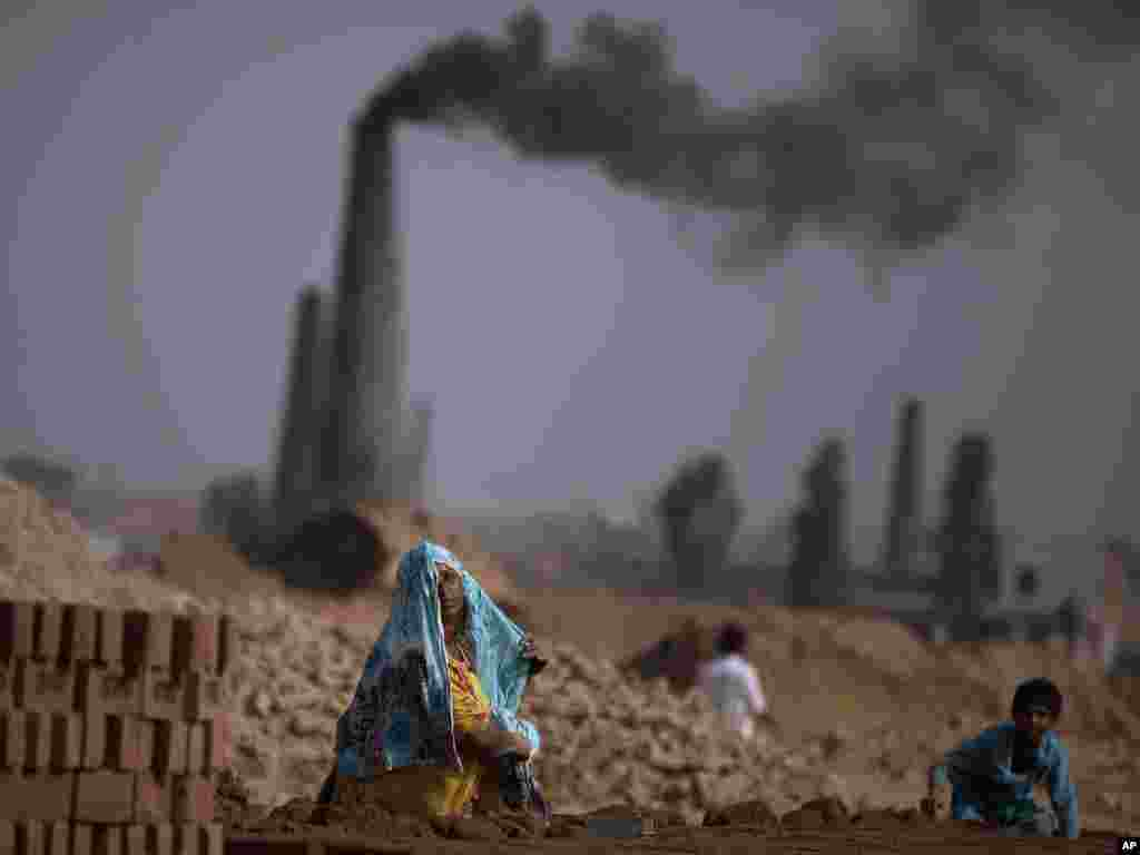 Pakistani Nazeeran Zafar, 38, adjusts her head scarf while working in a brick factory with her son Mohammad on the outskirts of Islamabad. Photo by Muhammed Muheisen for AP
